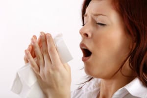 A Vancouver Washington Woman sneezes due to allergies before air duct cleaning