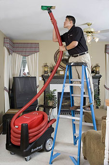 A technician on a ladder facilitating air duct cleaning in a Vancouver Washington home